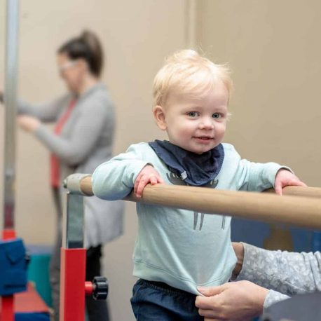 A toddler smiles at the camera whilst on parallel bars
